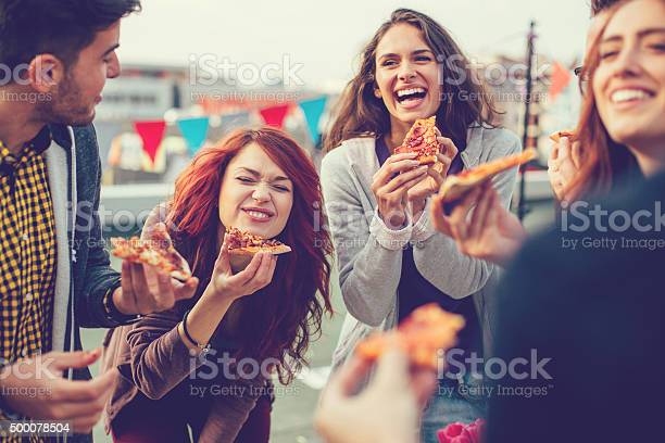 Young People Eating Pizza At Party Stock Photo - Download Image Now