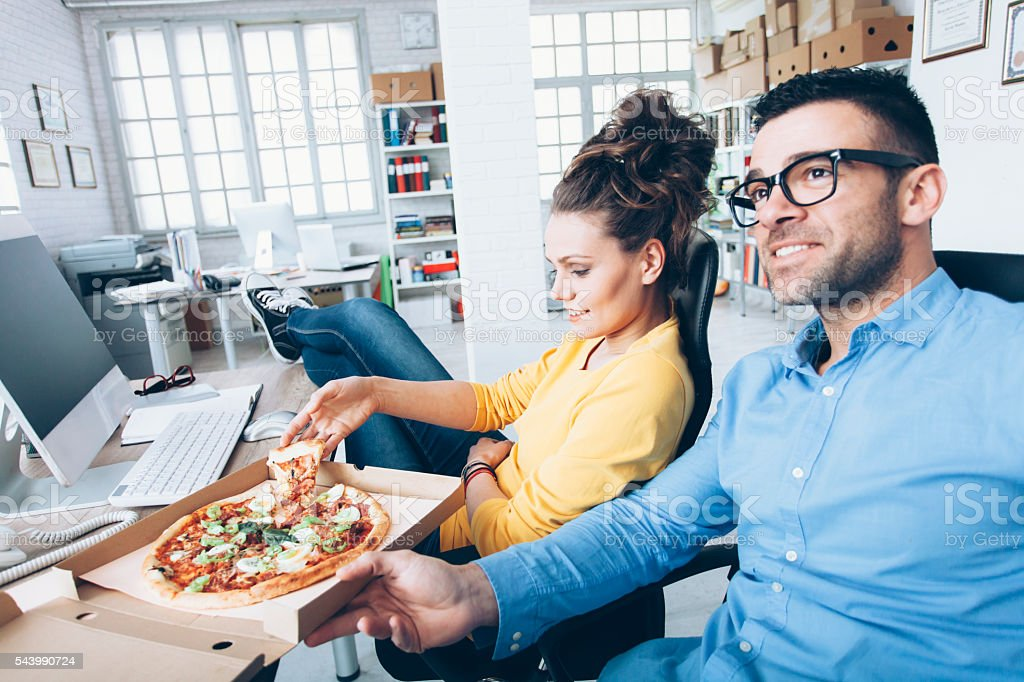 Young people eating pizza at workplace stock photo