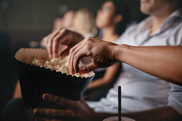 young people eating popcorn in movie theater - 映画館 ストックフォトと画像