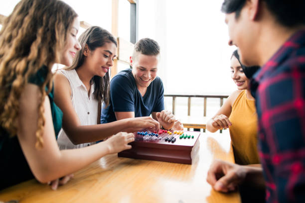 Young people enjoyig time with a boardgame stock photo