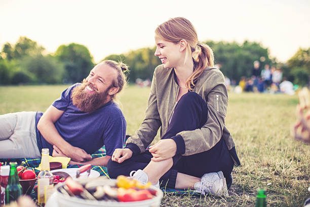 Young people enjoying picnic in park stock photo