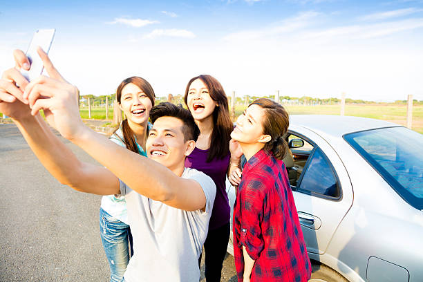 young  people enjoying road trip  and making selfie - asian travel in car stock photos and pictures