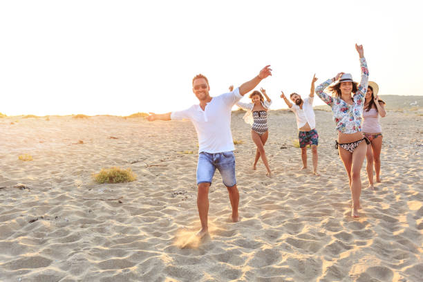 jonge mensen genieten van de zomervakanties - strandfeest stockfoto's en -beelden