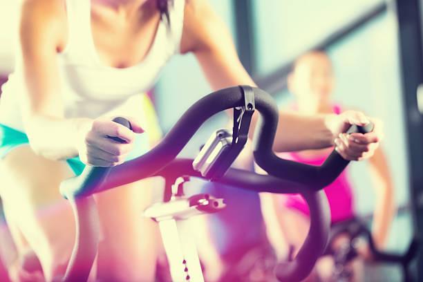 young people exercising in the fitness gym - ronddraaien stockfoto's en -beelden
