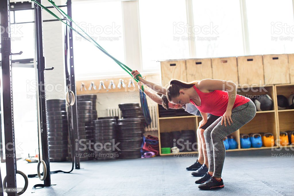 Young people exercising with resistance band in gym stock photo
