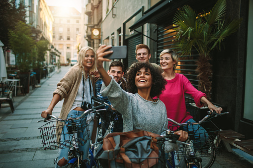 Group of young people exploring the city on bicycle and making selfie.