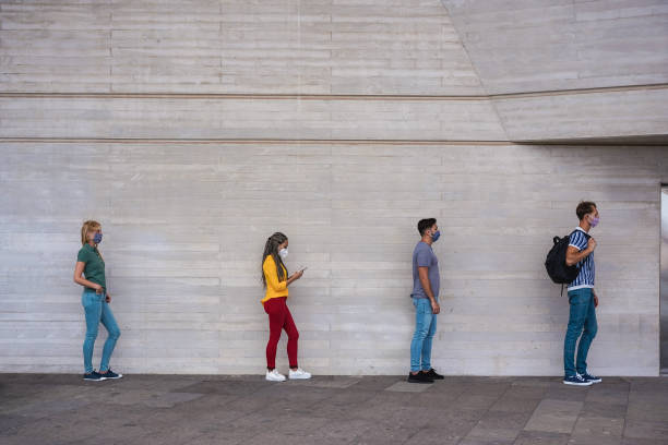 Young people friends bump their elbows instead of greeting with a hug - Avoid the spread of coronavirus, social distance and friendship concept - Focus on right girl eye stock photo