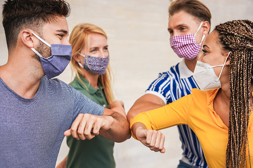 Young people friends bump their elbows instead of greeting with a hug - Avoid the spread of coronavirus, social distance and friendship concept - Focus on right girl eye