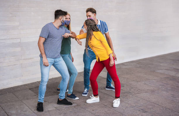 Young people friends bump their elbows instead of greeting with a hug - Avoid the spread of coronavirus, social distance and friendship concept - Main focus on left guy face stock photo