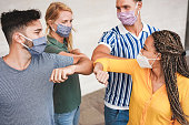 Young people friends bump their elbows instead of greeting with a hug - Avoid the spread of coronavirus, social distance and friendship concept - Focus on right woman face