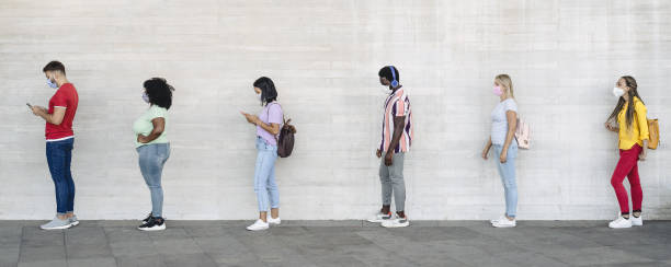young people from different cultures and race waiting in queue outside shop market while keeping social distance - corona virus spread prevention concept - afro latino mask imagens e fotografias de stock