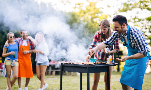 young people grilling outdoors - barbecue grill stock photos and pictures