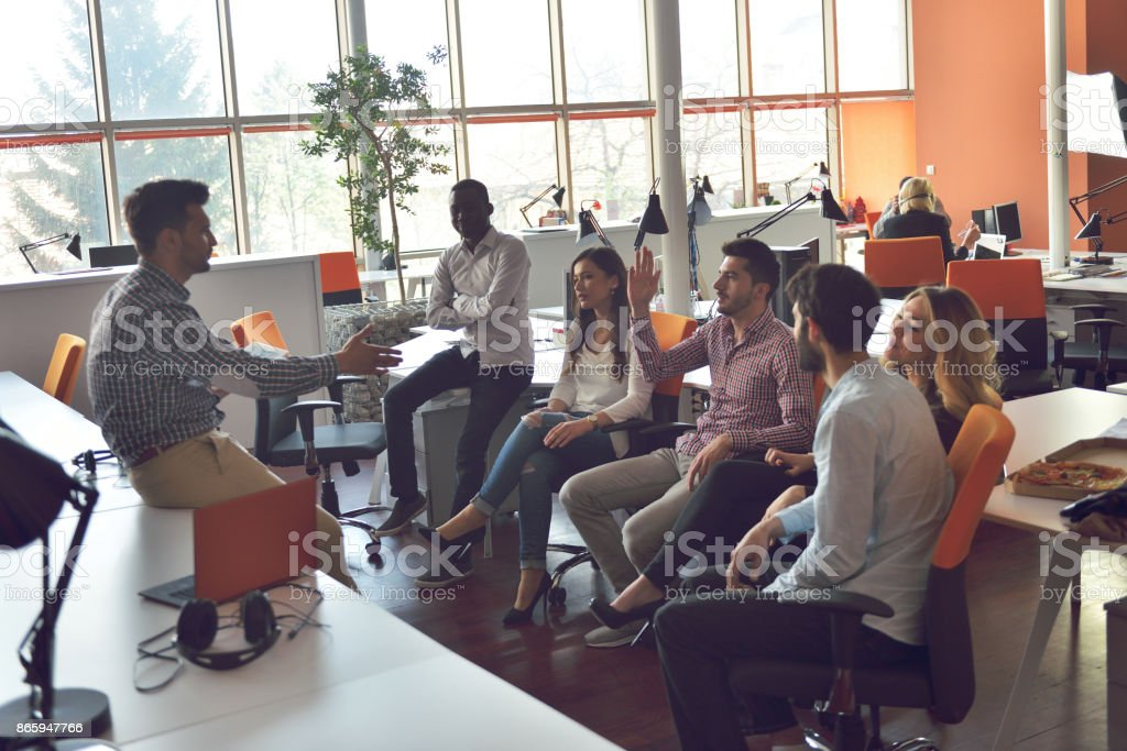 young people group in modern office have team meeting and brainstorming while working on laptop and drinking coffee stock photo