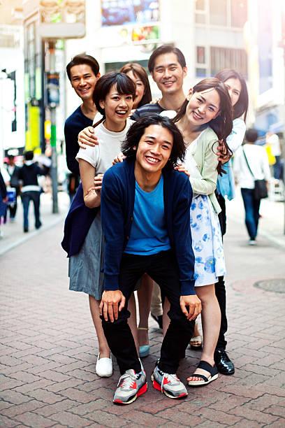 junge menschen abhängen gegen stadtbild, tokio. - happy weekend bilder stock-fotos und bilder