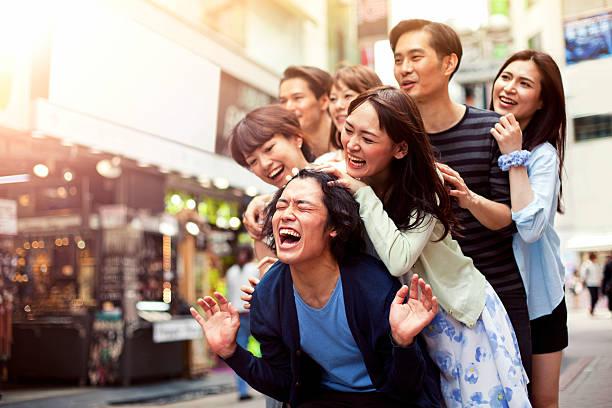 junge menschen abhängen gegen stadtbild, tokio. - asienreise stock-fotos und bilder