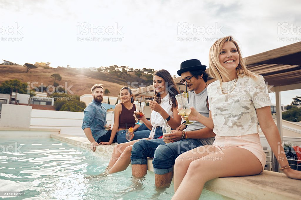Young people hanging out by swimming pool stock photo