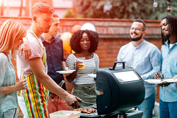 junge menschen havin spaß bei barbecue-party. - grillschürze stock-fotos und bilder