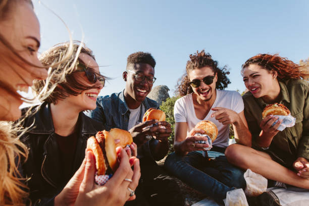 young people having a picnic on mountain top - eating stock pictures, royalty-free photos & images
