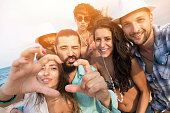 Group of young people having fun on the beach, making selfie. Girls with bikini, boys with casual clothes. Making faces and hand signs, heart shape. Sea and sky on background.