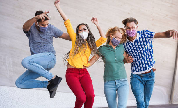 Young people having fun around city street during coronavirus outbreak - Happy friends wearing face protective masks and laughing together - Main focus on girls faces stock photo