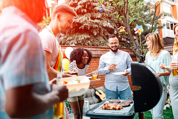 young people having fun at barbecue party. - barbecue grill stock photos and pictures