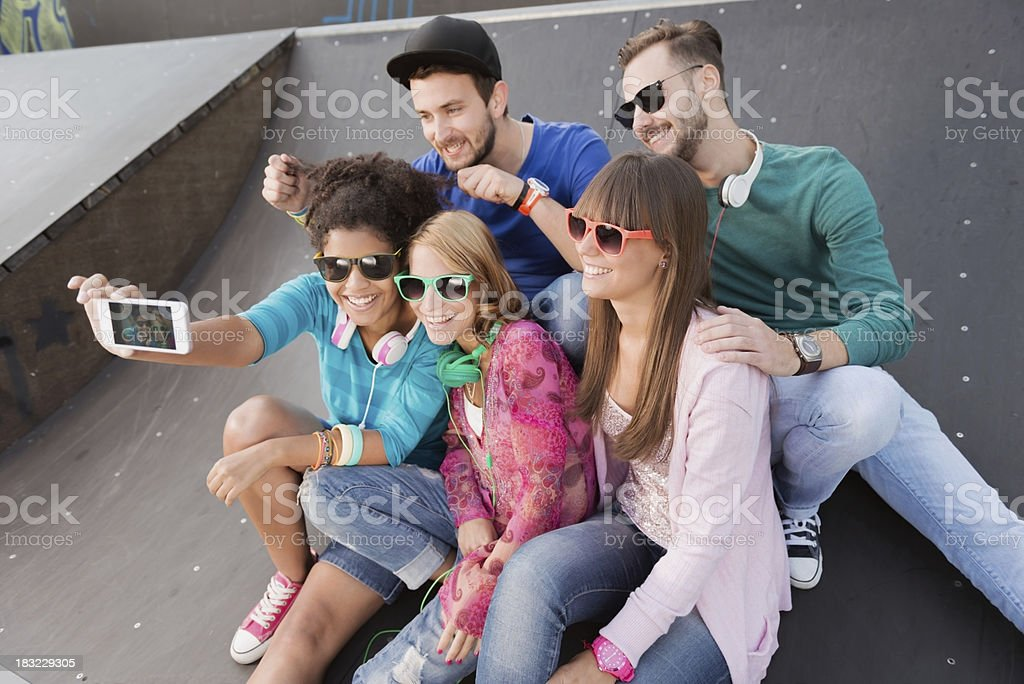 Young people having fun at the skatepark Young people sitting in a skate park, taking pictures Adolescence Stock Photo