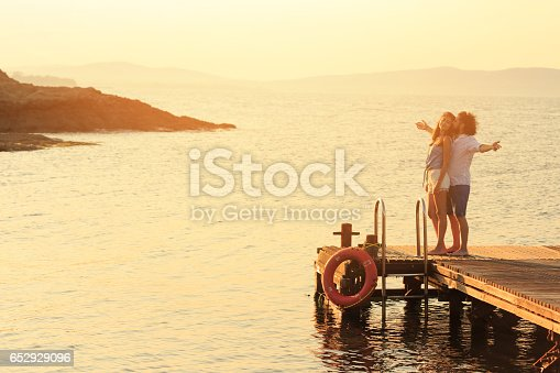 Young people having fun on a pier. Both with casual clothes, man with beard and curly hair, woman with long hair. Man with arms outstretched.