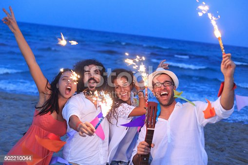 471113366istockphoto Young people having fun on the beach with fireworks 502210044