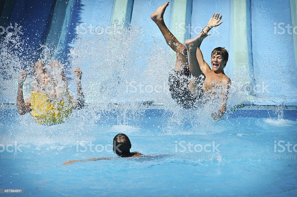 Young people having fun on water slides in aqua park stock photo
