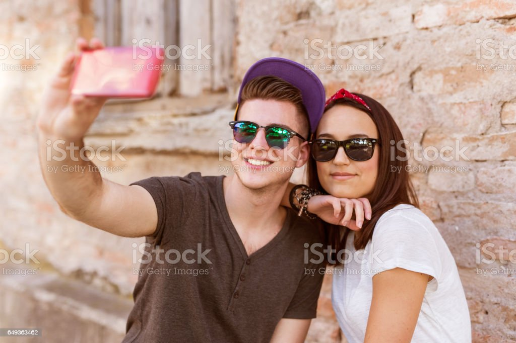 Young people having fun outdoor and making selfie with smart phone against red brick wall. Urban lifestyle, happiness, joy, friends. Instagram stock photo