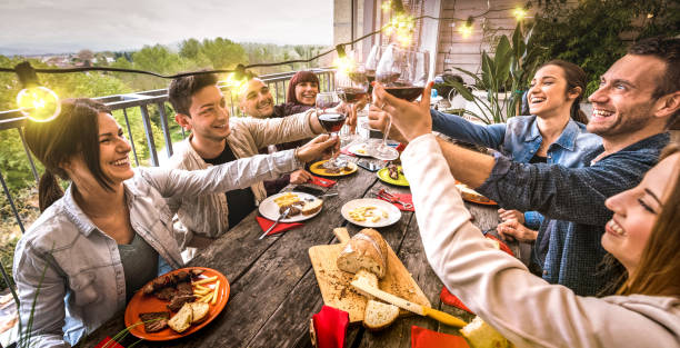 Young people having fun toasting red wine together at dinner party in outdoor villa - Happy friends eating bbq food at restaurant patio - Millennial life style concept on warm retro filter - Wide view stock photo