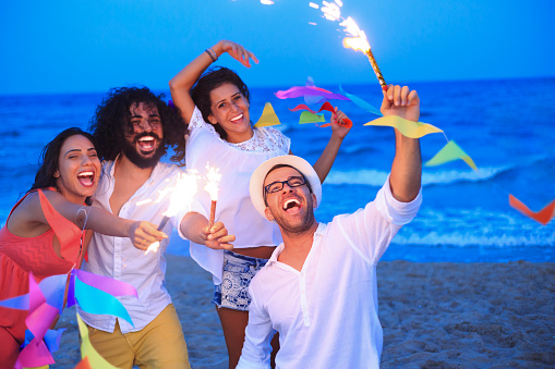 471113366 istock photo Young people having fun with fireworks and decoration on beach 502805324