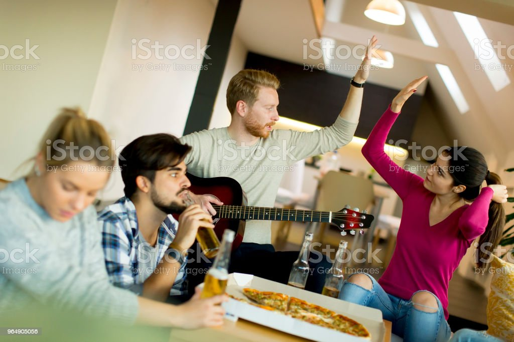 Young people having pizza party in the room royalty-free stock photo