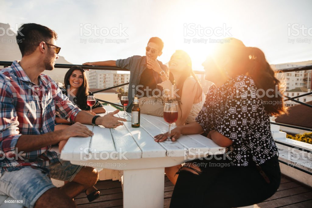 Young people having rooftop party in evening. stock photo