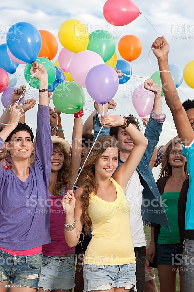 Young people holding balloons stock photo