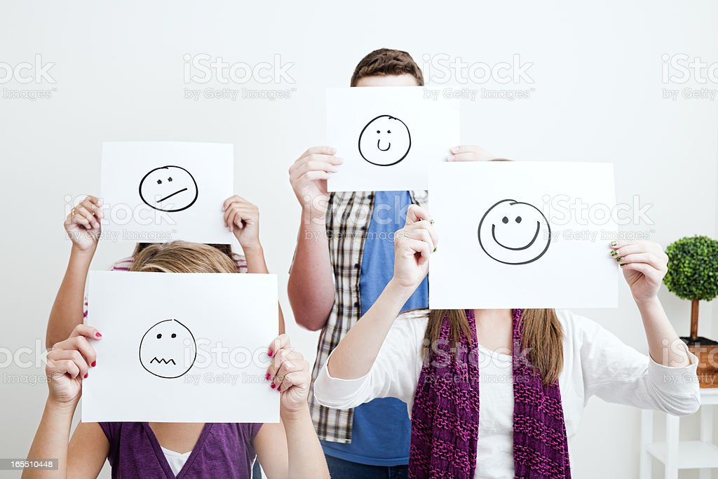 Young people holding cartoon faces in front of their faces royalty-free stock photo