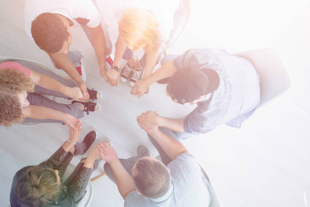Young people holding hands High angle of young people holding hands and sitting in the circle during group therapy drug rehab stock pictures, royalty-free photos & images