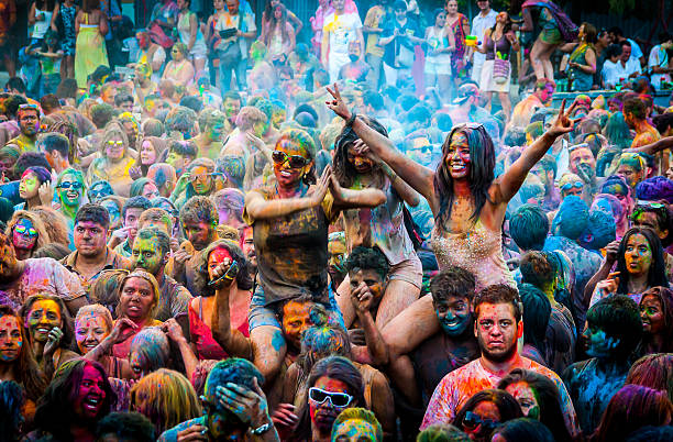 young people impregnated with colors at a holi party - indische gesichtsfarben stock-fotos und bilder