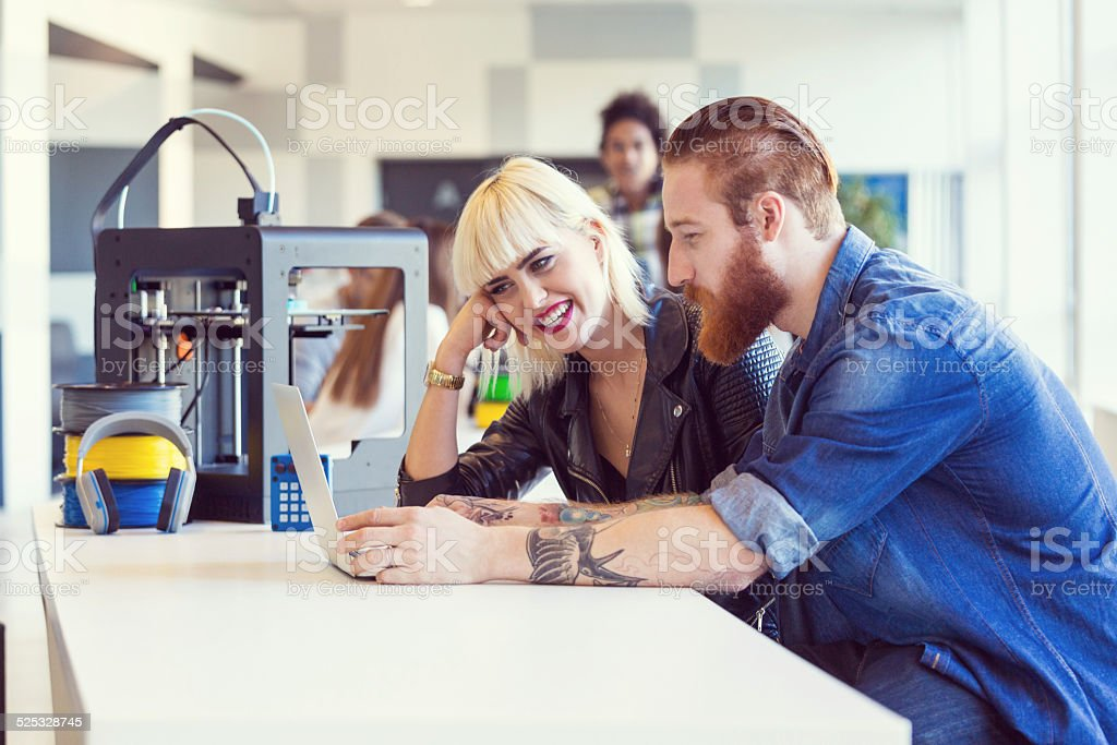 Young people in 3D printer office Start-up business team working in the 3D printer office, close-up of couple using laptop. 3D Printing Stock Photo