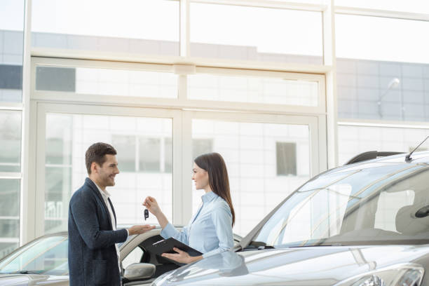 Young People in a Car Rental Service Transportation Concept Young man and woman in a car rental service signing contract car salesperson stock pictures, royalty-free photos & images