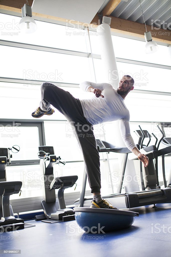Young people in gym - kicking on balance training equipment stock photo