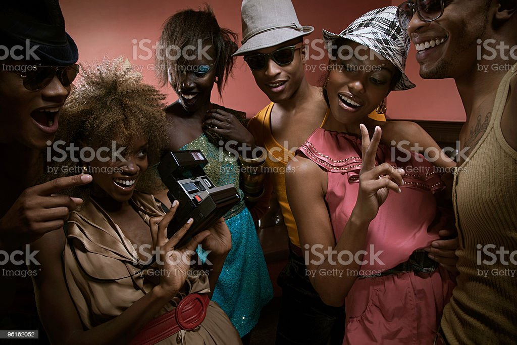 Young people in nightclub with instant camera stock photo