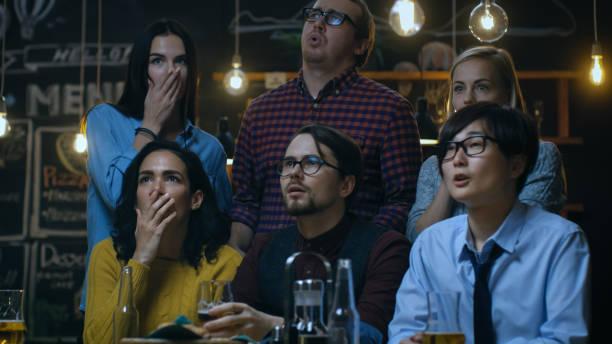 junge leute in der bar watch tv plötzlich breaking news show dieser tragischen ereignisse entfalten. junge menschen sind entsetzt, traurig und schockiert. - zum totlachen stock-fotos und bilder