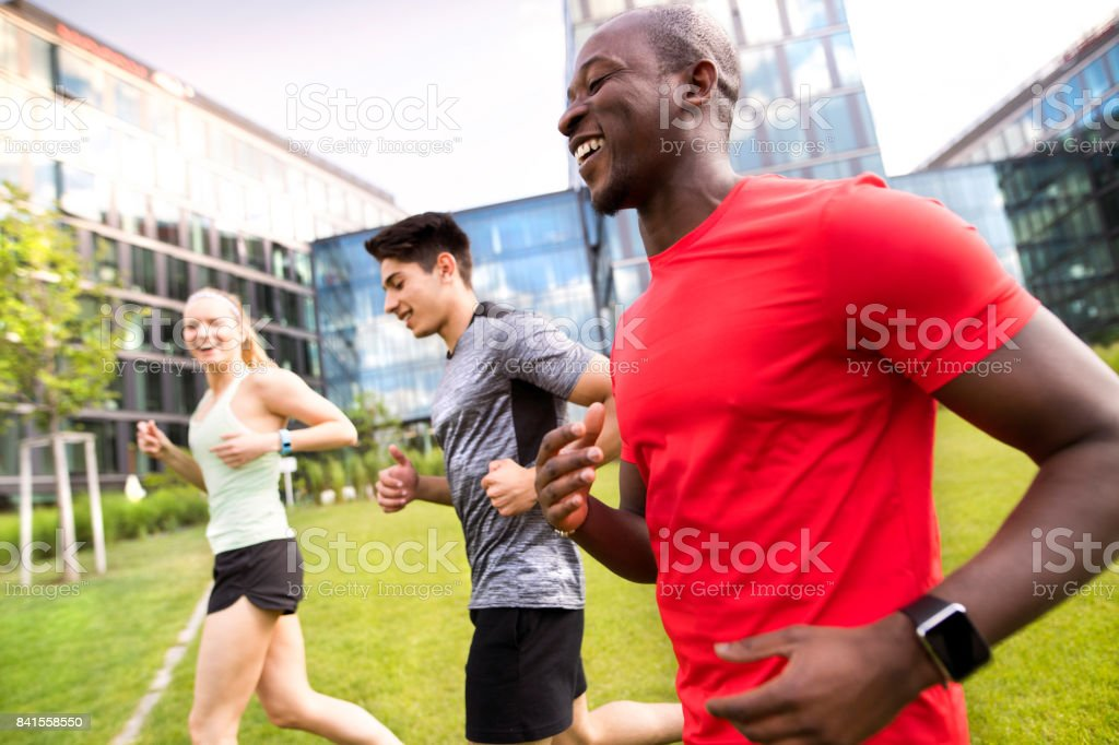 Young people in the city running together. stock photo