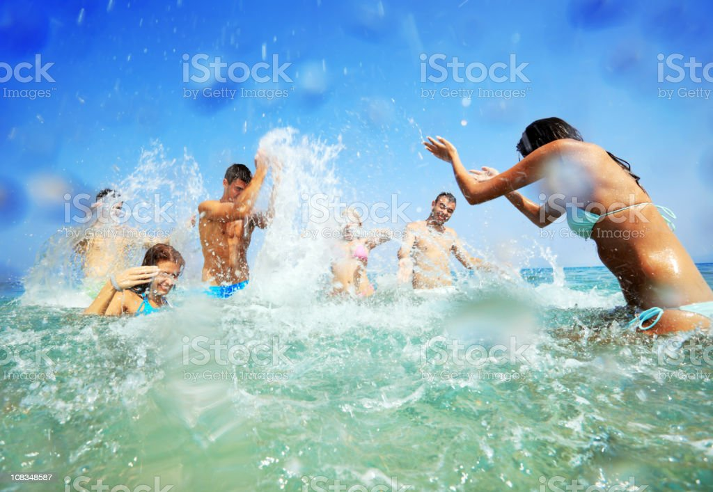Young people in water spraying each other. royalty-free stock photo