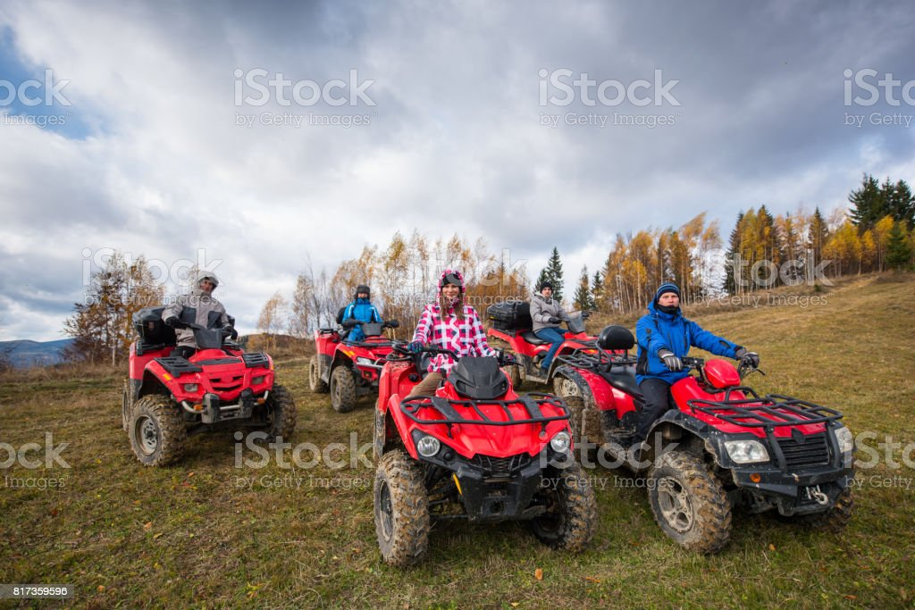 Young people in winter clothes on red atv off-road vehicles on a countryside trail in nature under the sky with clouds stock photo