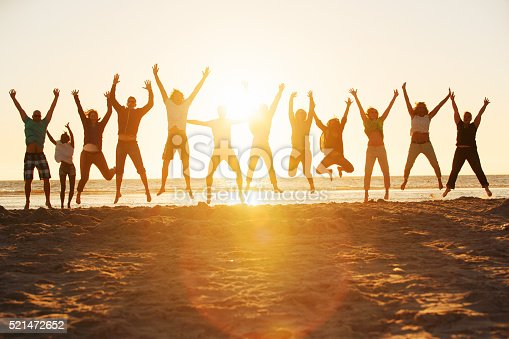 istock Young people jumping at the beach of St.Peter-Ording in Germany 521472652