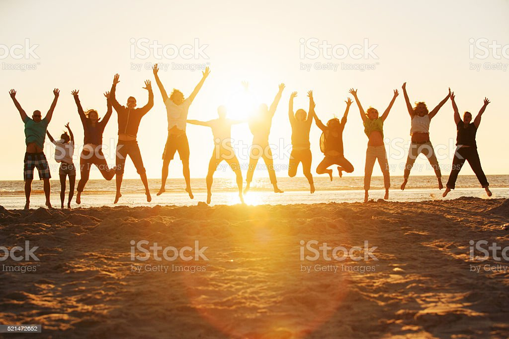 Young people jumping at the beach of St.Peter-Ording in Germany stock photo