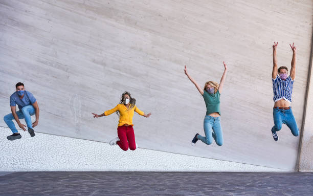Young people jumping dancing outdoor during coronavirus outbreak - Happy friends wearing face protective masks and having fun together - Social distancing and happiness concept - Main focus on faces stock photo