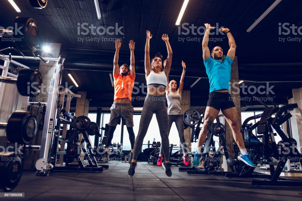 Young people jumping during fitness class at the gym stock photo